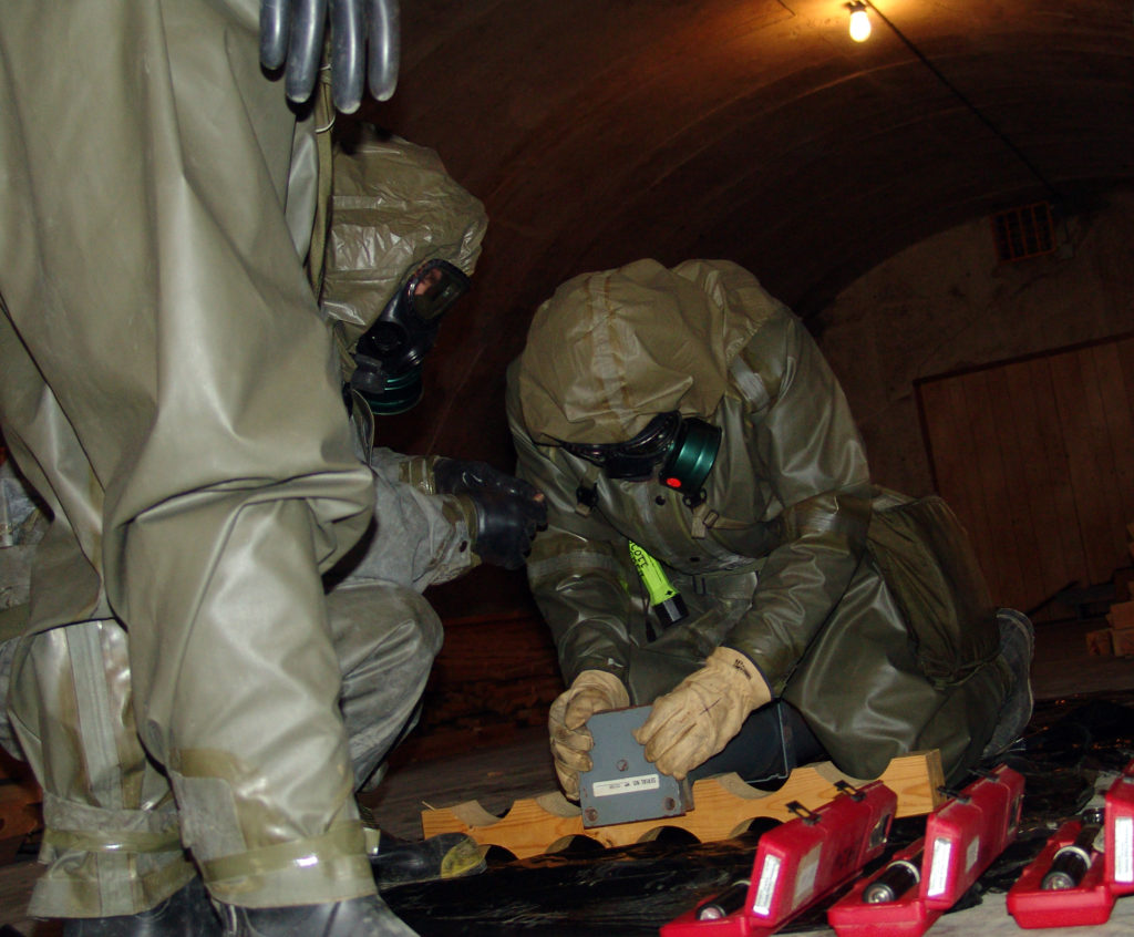 Men in protective suits working on munitions